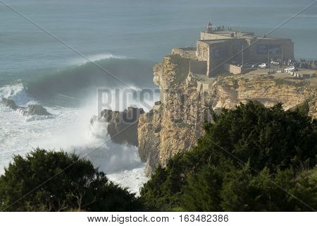 NAZARE PORTUGAL - Dec 17 2016: Spectators on and around the lighthouse at the Praia do Norte in Nazare Portugal to see huge XXL waves.