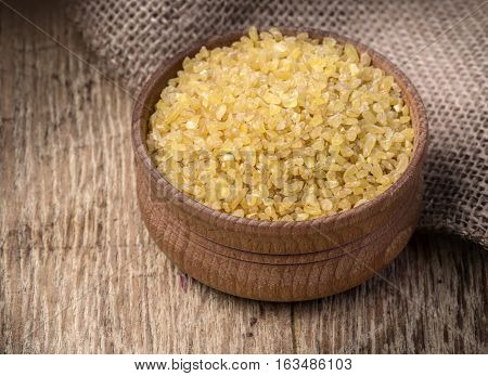 Raw Bulgur (on wooden background) as detailed close-up shot