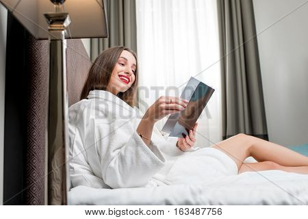 Young woman in bathrobe reading magazine on the bed in the hotel room or bedroom
