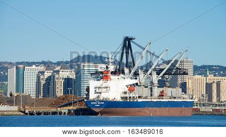 Oakland CA - December 28 2016: Bulk Carrier AURORA BULKER loading at the Port of Oakland. Schnitzer Steel recycles scrap metal into finished steel products such as rebar and wire rod.