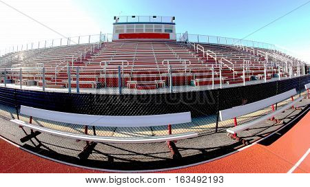 A fish eye photo of a local high school athletic stadium bleechers benches and track