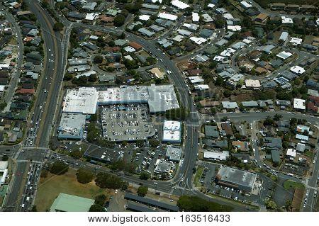 Aerial of Likelike Highway Kam Shopping Center surrounding Neighborhood with homes Condos and school on Oahu Hawaii.