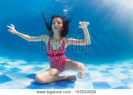 Funny portrait of girl swimming and diving in blue pool with fun - jumping deep down under water. Underwater swimming lesson. Family lifestyle and summer children water sports activity with parents.