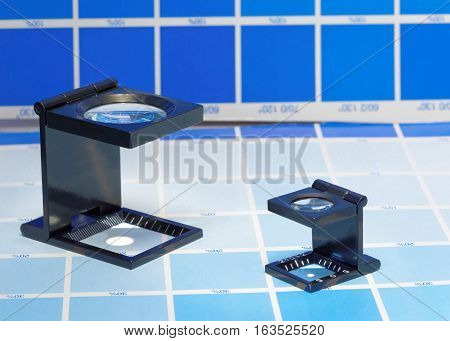 Two magnifier or printer's loupe sits on a cyan test sheet in a pre-press workshop