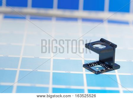 Magnifier or printer's loupe sits on a cyan test sheet in a pre-press workshop