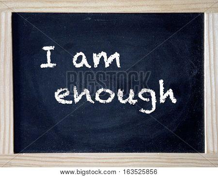 the words I Am Enough written on black chalk board