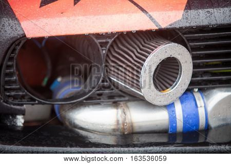 Color image of a tuned car air filter and exhaust pipe.