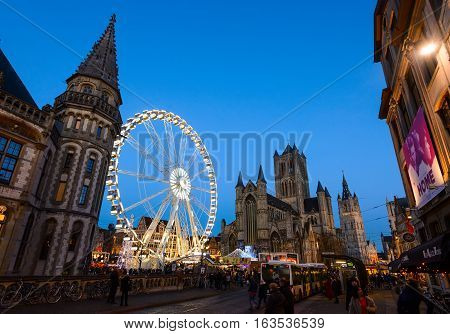 Ghent, Belgium - December 27th, 2016. Gent city winter festival in Flanders. Christmas fair with ferris wheel and festive decorations near Saint Nicholas Church on the Ghent Old town square.