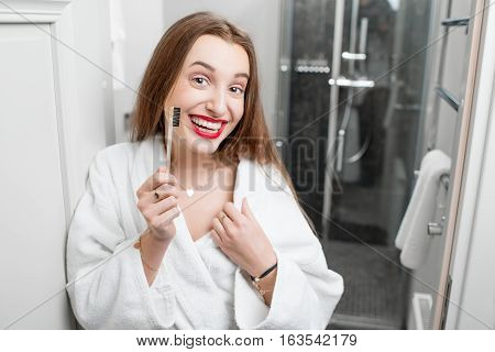 Portrait of smiling woman in bathrobe with toothbrush in the bathroom