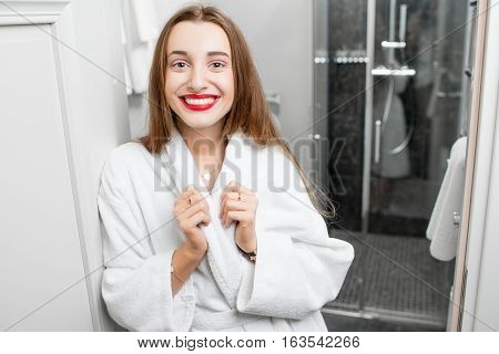 Portrait of young smiling woman in bathrobe in the bathroom