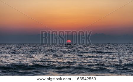 The lonely fisherman stands in the boat against the background of the sunset in the middle of the Indian Ocean. The sun falls directly to water on the center of a shot.