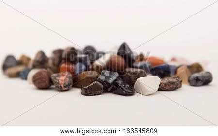 Scattering of colorful smooth stones. White background. Collection of stones. Round precious and semi-precious minerals. Polished minerals. Beautiful natural stones.