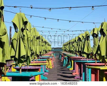 Brightly coloured umbrellas on a seaside patio with tables and stools