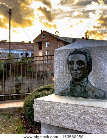 Prattville Alabama USA - December 26 2016: Bust of Daniel Pratt the founder of Prattville with the Continental Eagle Cotton Gin Company in the background.