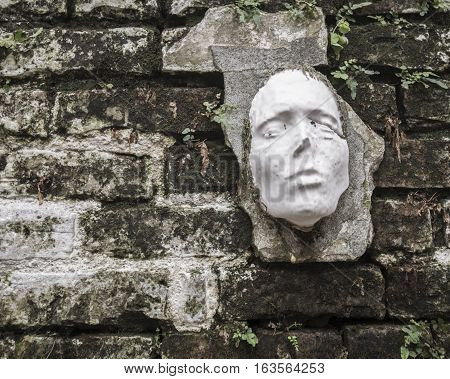 Unusual and strange face sculpture mounted on an old brick wall.