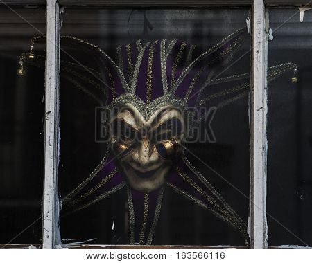 Color image of a Mardi Gra mask in the window - French Quarter of New Orleans Louisiana