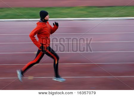 Woman running on the track, intentional motion blur