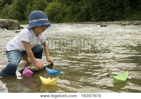 Cute girl playing with paper boats