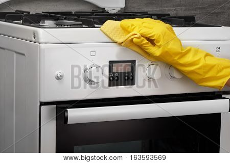 Hand In Yellow Glove Cleaning White Stove With Rag