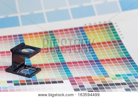 Magnifier or printer's loupe sits on a colorful CMYK test sheet in a pre-press workshop