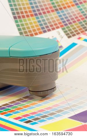 Spectrometer used for proofing on a leaf of the cmyk test print in a pre-press workshop