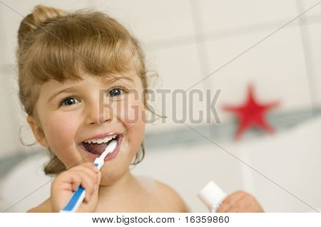 Little girl brushing teeth in bath