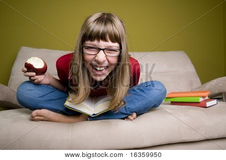 Happy teenage girl  with book on a sofa.
