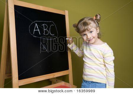 Cute little girl at blackboard