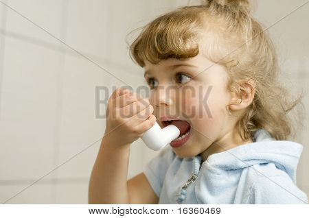 Little girl using inhaler