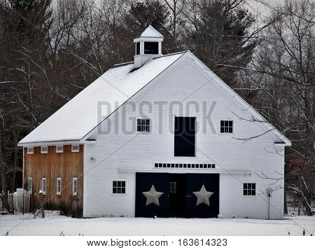 Large snow covered New England barn with cupola and star decorated doors