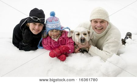 Family with dog playing on winter