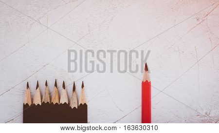 Red pencil standing out from crowd of plenty identical black fellows on white table. Leadership, business success concept