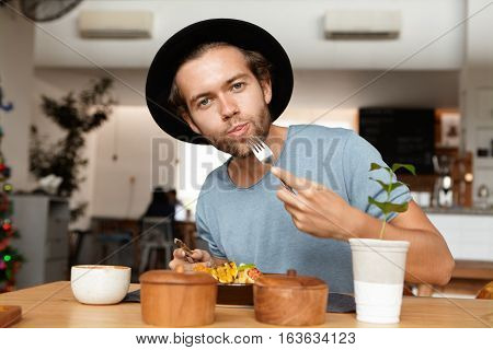 People, Food And Lifestyle Concept. Indoor Shot Of Attractive Young Student Wearing Black Hat And Bl
