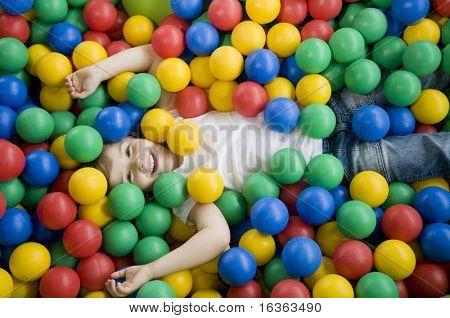 Menina feliz jogando em bolas coloridas
