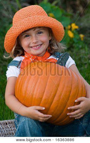 Little girl with big pumpkin