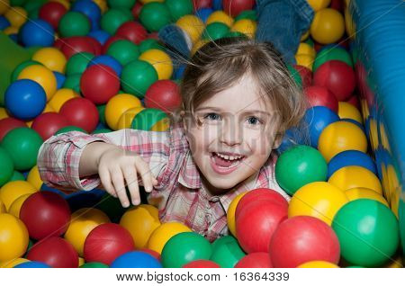 Happy girl playing in colorful balls