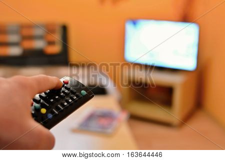 Holding the TV remote control and switching the channel on television.