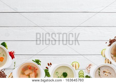 Empty wooden table with variation of soups flat lay. Top view on white wooden background with different restaurant hot dishes, free space. Worldwide cuisine, healthy food, buffet, lunch, menu concept