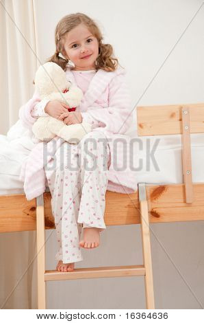 Cute girl in pyjama hugging no-name teddy bear
