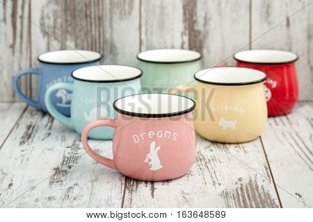 Colorful ceramic mugs with enamel look on white wooden background