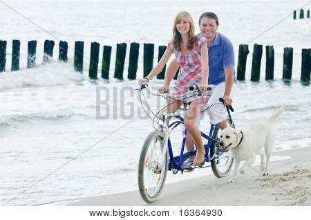 Happy tandem with dog  at the beach