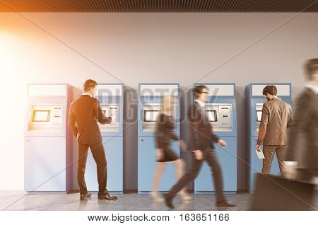 Two men are withdrawing money from ATM machines in a hall of a bank or an office. Their colleagues are passing by. Toned image