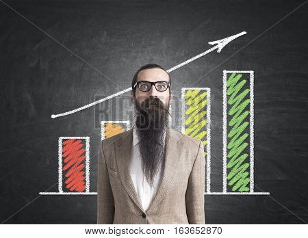 Portrait of a baffled businessman with a long beard standing in a beige suit near a blackboard with a colorful graph. Concept of success