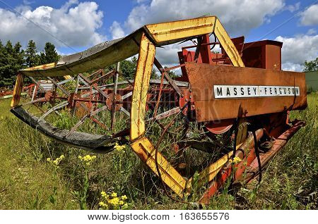 DETROIT LAKES, MINNESOTA, August 5, 2016: The Massey Ferguson name on the self propelled swather with a huge wheel appeared when a merger of Massey Harris and the Ferguson Company farm machinery manufacturer occurred in 1953 and is now owned by AGCO.