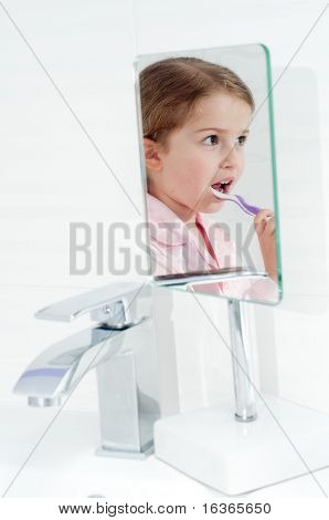 Little girl brushing teeth in bathroom