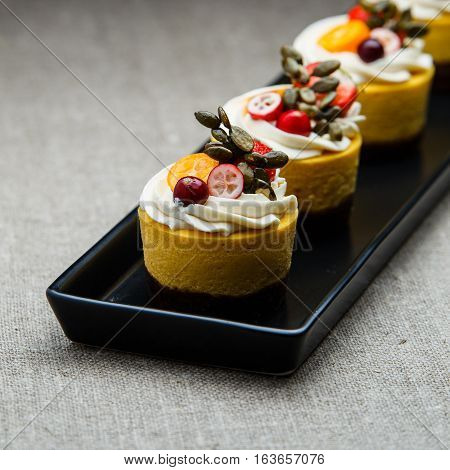 Delicious pumpkin cupcakes on black dish with grey background