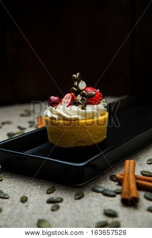 Delicious pumpkin cupcakes on black dish with seeds around