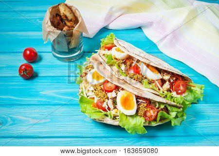 Pita sandwich stuffed with chicken egg salad cheese cherry tomato on blue wood.