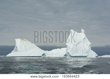ancipitate iceberg in Antarctic waters on a cloudy day