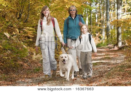 Family autumn trekking with dog